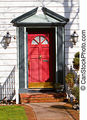 Red front door with gray border of home in a residential...