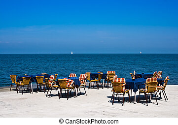 Slow Business - Empty chairs and tables at the seaside