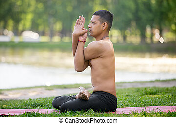 Variation of Padmasana in park - Serene Indian young man...