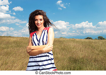 Smiling young lady holding her hands crossed