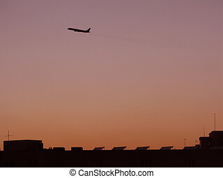 Airplane takeoff at dusk against red skies and rooftop...