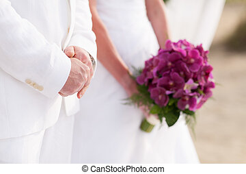 Bride holding bouquet of orchid in wedding ceramony