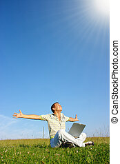 Student with laptop on green meadow - Happy student with...