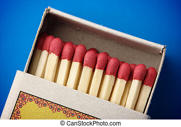 Red matchsticks in the box on blue background, shallow DOF