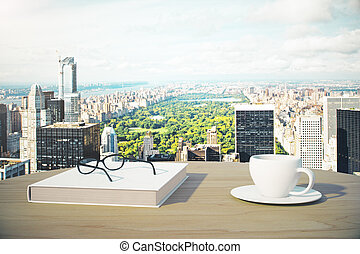 Great city view with cup of coffee, book and glasses outdoor