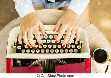 Girl typing on the old typewriter with a cup of coffee...