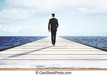 Businessman walking on a straight road to the horizon