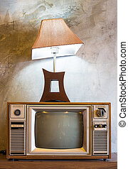 retro tv with wooden case and lantern in room with vintage wallpaper on wood table