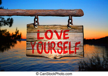 Love yourself sign with sunset blurred background