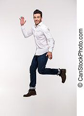 Portrait of a funny man jumping isolated on a white...