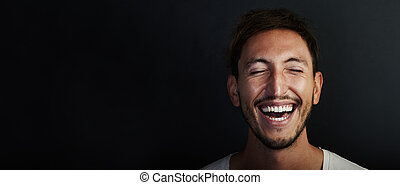 Portrait of cute young man wearing white tshirt and laughing...
