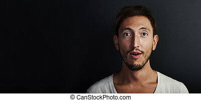 Portrait of young man wearing white tshirt and looks...