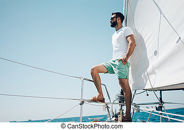 Low angle view of young bearded man standing on the nose...