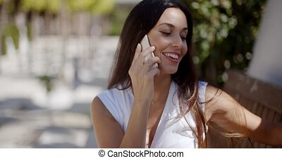 Vivacious young woman chatting on her mobile