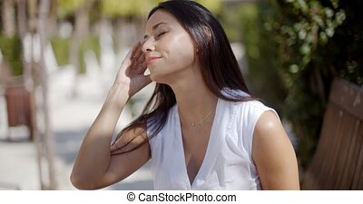 Young woman suffering from a headache pausing in an urban...