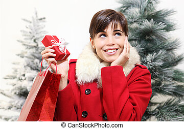 smiling woman with Christmas gift, looks up, with trees in the background