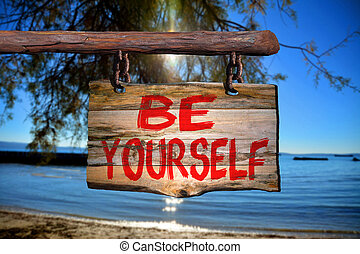 Be yourself sign with beach blurred background