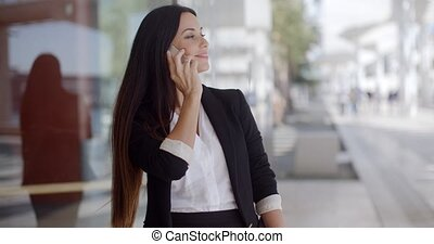 Thoughtful gorgeous woman chatting on a mobile phone in an...