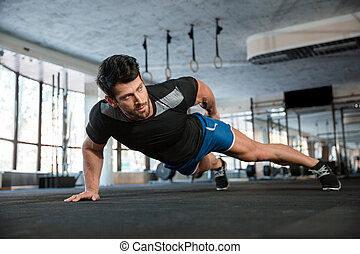 Handsome man doing push ups exercise - Portrait of a...