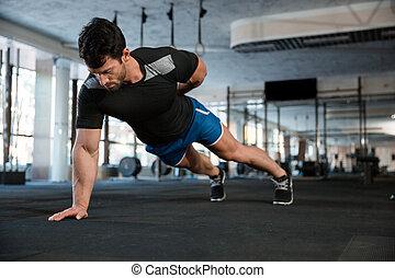 Athlete doing one hand push-ups - Athlete wearing blue...