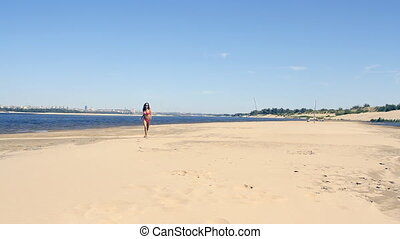 tanned young woman running on the beach at sunny day