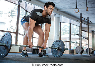 Athlete lifting barbell - Athlete wearing blue shorts and...