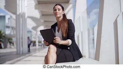 Elegant business manageress working on a laptop as she...