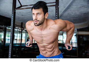 Handsome man doing exercise on parallel bars - Portrait of a...