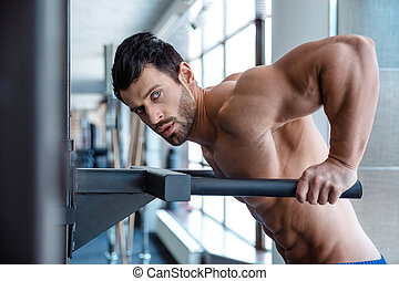 Muscular man workout on parallel bars - Portrait of a...