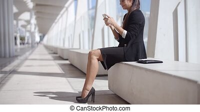 Elegant businesswoman reading her text messages on her...
