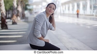 Pretty woman sitting beside a pedestrian walkway - Pretty...