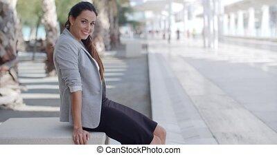Elegant woman sitting on a bench on a promenade