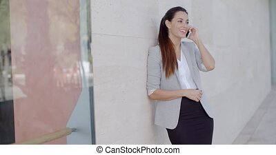Happy relaxed young woman chatting on her mobile