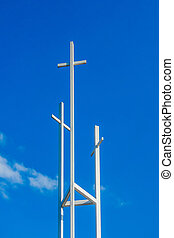 Three trinity White Christian crosses in front of a cloudy...
