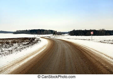 winter road snow - small country road passes in a field in...
