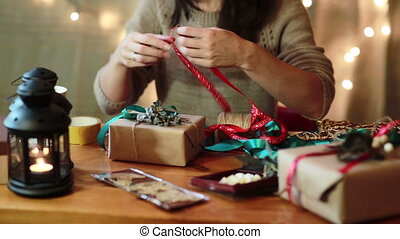 Young Woman Wrapping Christmas Gifts At Home - Young Woman...