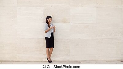 Stylish businesswoman standing against a wall - Stylish...