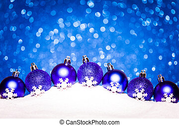 christmas blue balls in snow on glitter background
