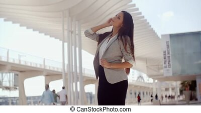 Stylish woman with long hair standing on a mobile - Stylish...