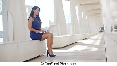 Elegant businesswoman working outdoors sitting on a white...