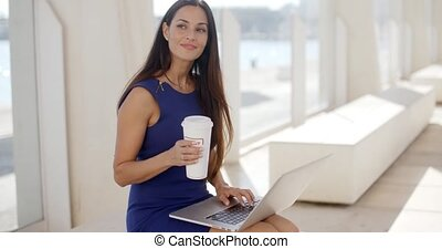 Happy successful young businesswoman sitting on an outdoor...