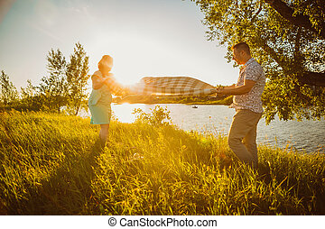 Romantic couple put a blanket on background summer lake