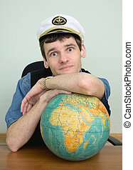 Young man in a captain\'s cap with globe