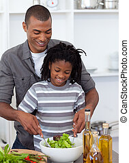 Smiling father helping his son cut vegetables in the kitchen