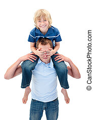 Smiling son with his father enjoying piggyback ride against...