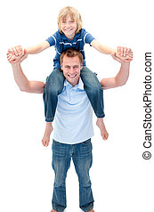 Smiling father giving his son piggyback ride against a white...