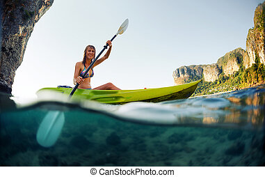 Young lady paddling the kayak in a bay with limestone...