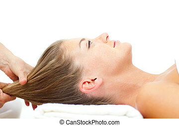 Relaxed woman enjoying a hair massage in a spa center