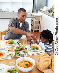 Pensive father having dinner with his son in the kitchen