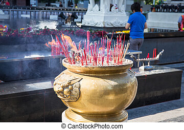 Smoking incense sticks at central world bangkok thailand. The incense is lit as an offering to the gods.
